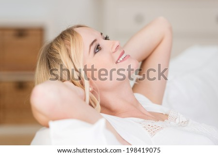 Pretty blond woman lying daydreaming on a sofa with her hands clasped behind her head and a happy contented smile as she stares into the air - stock photo