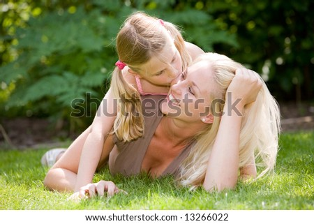 Pretty blond woman lying in the grass with her daughter, who is giving mum a kiss - stock photo
