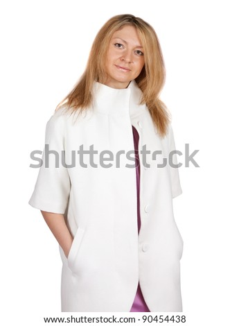Pretty blond woman on white backdrop in white coat - stock photo