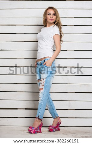 Pretty blond woman posing in blue ripped jeans and white t-shirt near wooden wall - stock photo