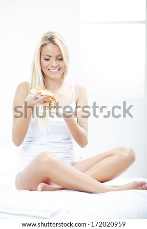 Pretty Blond Woman, sitting and eating pizza while looking down - stock photo