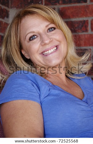 Pretty blond woman smiling happy - stock photo