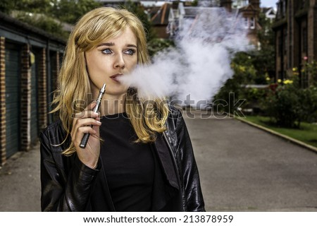 Pretty blond woman smoking an e-cigarette standing in a street in a leather jacket exhaling a cloud a smoke from her mouth while looking off to the side - stock photo