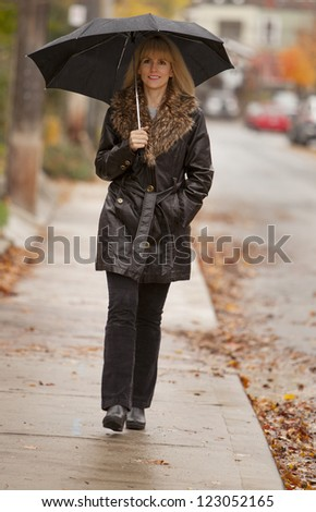 Pretty blond woman walking in rain with umbrella - stock photo