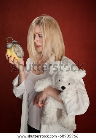 Pretty blond woman with bear and clock wakes up late - stock photo
