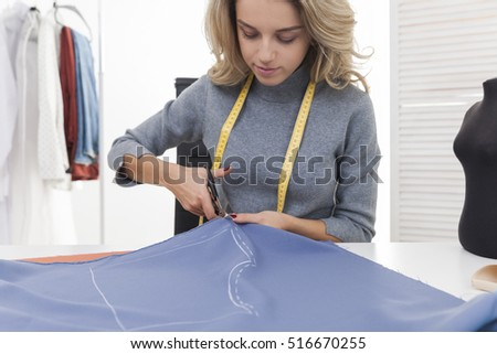 Pretty blond woman with measuring tape is cutting a pattern out of blue tissue. Concept of tailoring