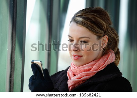 Pretty Blond Young Business Woman Using A Smartphone Wearing A Winter Coat Scarf And Gloves - stock photo