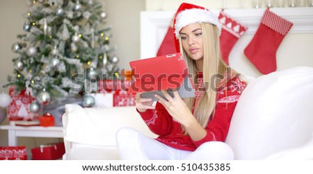 Pretty blond young woman sitting on couch with touchpad