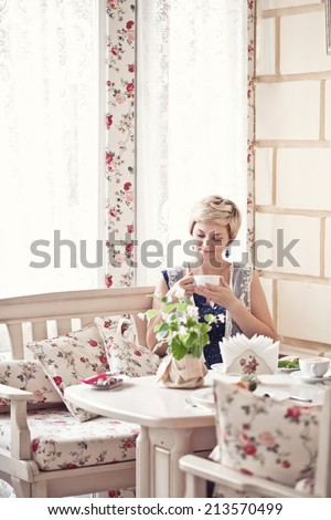 Pretty blond young woman with cup of cappuccino in the cozy cafe - stock photo