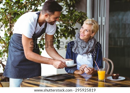 Pretty blonde being served a cup of coffee at the cafe - stock photo