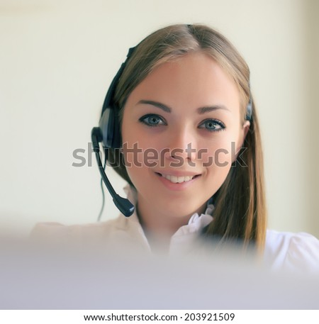 pretty blonde business woman with headset on a light background - stock photo
