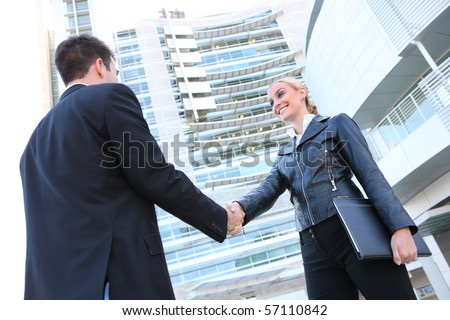 Pretty blonde caucasian business woman shaking hands with a man in her office - stock photo