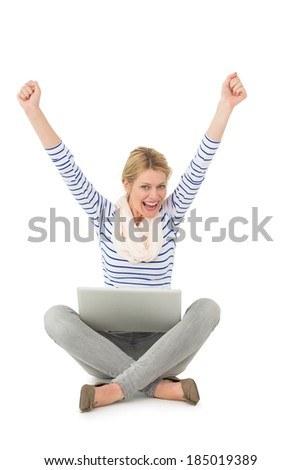 Pretty blonde cheering at camera with laptop sitting on floor on white background - stock photo