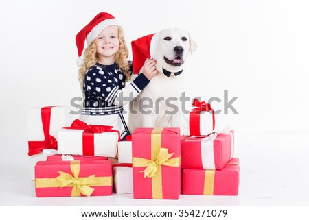 Pretty blonde child girl with her friend white labrador retriever are sitting with gifts isolates on white in studio - stock photo