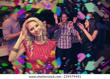 Pretty blonde drinking a cocktail against flying colours - stock photo