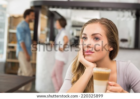 Pretty blonde enjoying a latte at the coffee shop - stock photo