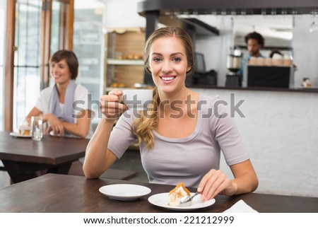 Pretty blonde enjoying cake and coffee at the coffee shop - stock photo