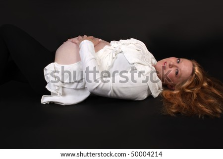 Pretty blonde expecting woman in her thirties laying down on a black background holding her pregnant belly