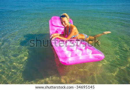 Pretty blonde girl floating on inflatable raft