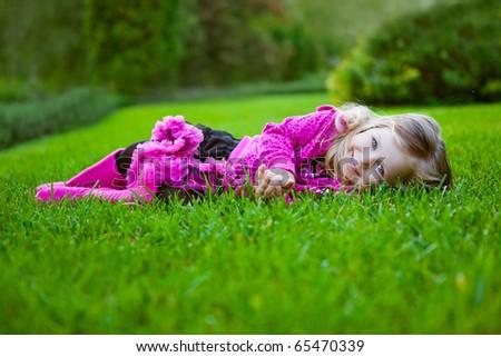 pretty blonde girl in pettiskirt lies on a grass - stock photo