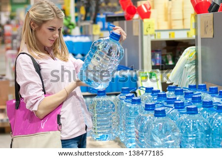 Pretty blonde girl in shop selecting clean water - stock photo