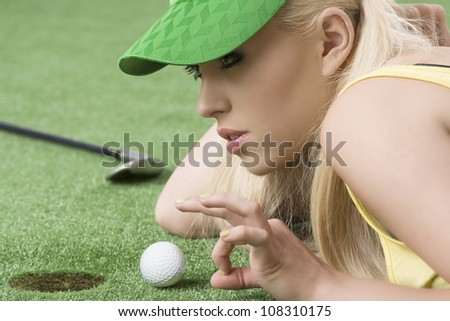 pretty blonde girl is lying on the grass and playing with golf ball, she is about to hits the ball with left hand - stock photo