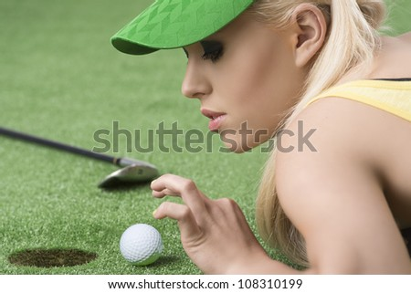 pretty blonde girl is lying on the grass and playing with golf ball, she is in profile and looks the ball - stock photo