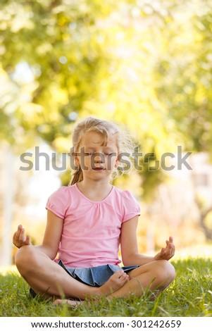 Pretty blonde girl meditating in yoga pose in park - stock photo