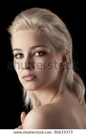 pretty blonde girl on black looking over her shoulder in the camera - stock photo