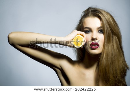 Pretty blonde girl portrait with bright make up looking forward holding half of fresh juicy orange standing on gray background copyspace, horizontal picture - stock photo