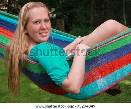 Pretty blonde girl relaxing in a hammock on a summer day