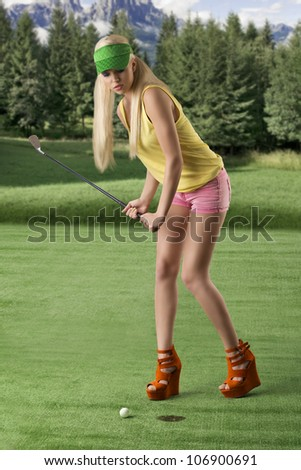 pretty blonde girl's playng golf with golf club, pink shorts and green sunshade, she is turned of three quarters at right and she is hitting the golf ball - stock photo
