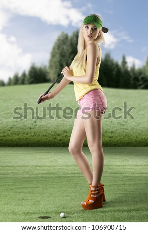 pretty blonde girl's playng golf with golf club, pink shorts and green sunshade, she is turned of three quarters at right, looks in to the lens with sexy expression and takes the golf club - stock photo