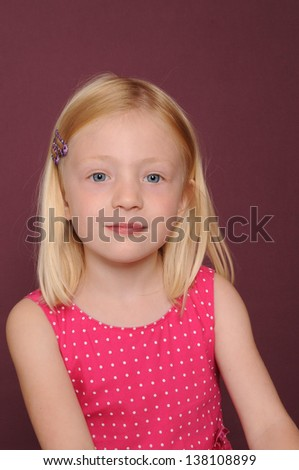 pretty blonde girl smiling isolated on plum background