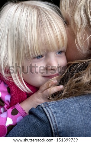 pretty blonde girl smiling while cuddling her mum