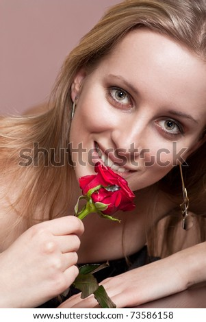 Pretty blonde girl with a flower - stock photo