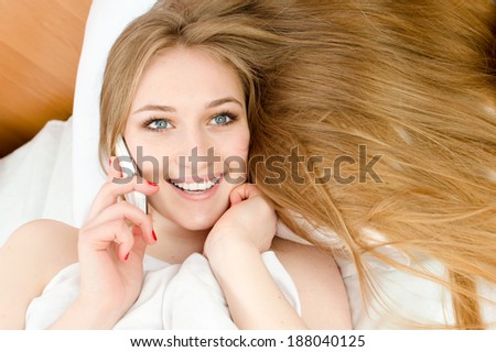 pretty blonde girl with blue eyes, red nails & white teeth lying in white bed talking on the mobile cell phone happy smiling & looking at camera portrait - stock photo