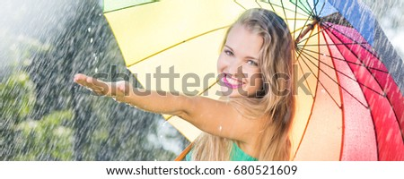 Pretty blonde girl with colorful umbrella during rain during summer