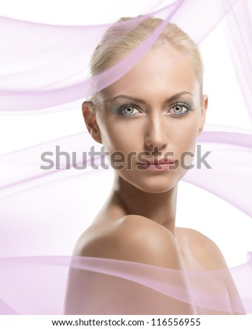 pretty blonde girl with naked shoulders, her body is turned of three quarters at left and she looks in to the lens - stock photo