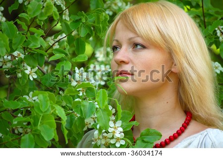 Pretty blonde girl with red beads near blooming pear-tree