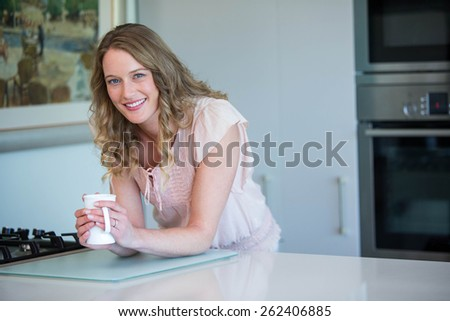 Pretty blonde holding a mug at home in the kitchen