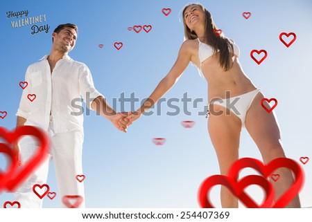 Pretty blonde holding hands with boyfriend against cute valentines message - stock photo