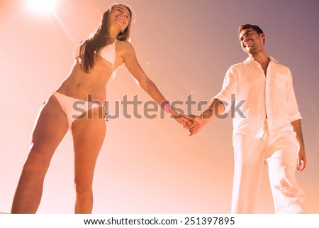 Pretty blonde holding hands with boyfriend on the beach - stock photo