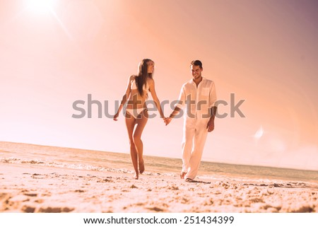 Pretty blonde holding hands with handsome boyfriend on the beach - stock photo