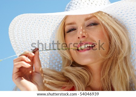 Pretty blonde in elegant hat looking at camera against blue sky - stock photo