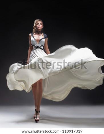 Pretty blonde in fluttering dress - stock photo