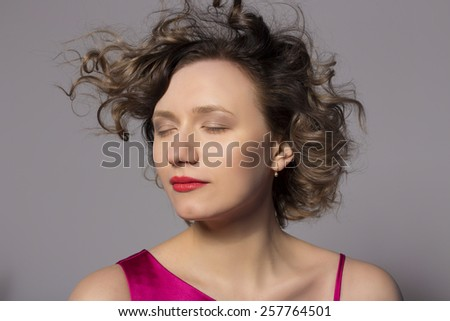 Pretty blonde in the studio on a gray background - stock photo