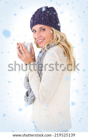 Pretty blonde in winter fashion holding mug against snow falling