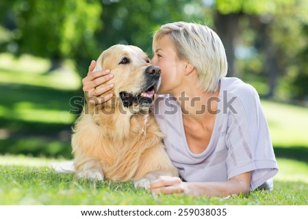 Pretty blonde kissing her dog in the park on a sunny day - stock photo
