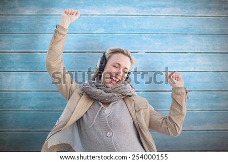 Pretty blonde listening to music against wooden planks - stock photo